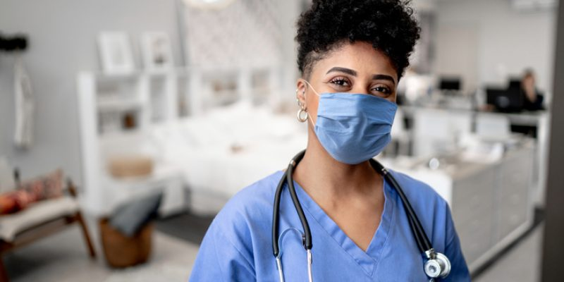 Portrait of a young nurse/doctor on a house call with face mask