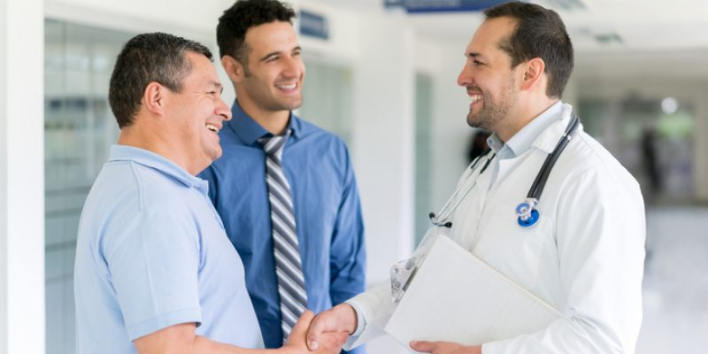 Doctor greeting patient with a handshake at the hospital and medical insurance agent standing there
